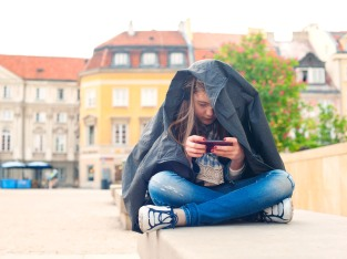 Teenage problems. Young girl addicted to social media technologies. Multicolored summertime outdoors horizontal image.